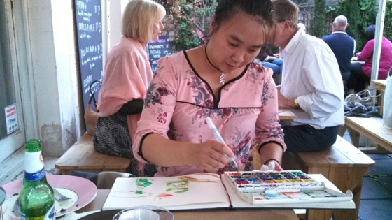 Me drawing at Ruby Red Flmingo. Photo courtesy of Kaz e Dru.